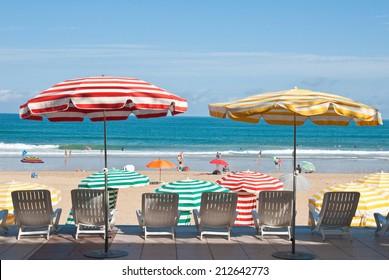 Striped umbrellas on the beach, facing the ocean, Biarritz, France