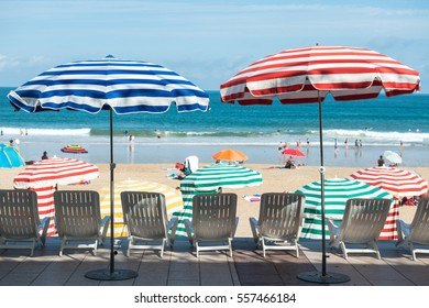 Striped umbrellas on the beach, facing the ocean, Biarritz, France
