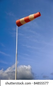 A striped weather vane at the airfield against blue sky