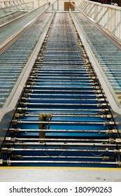 Stripped down people mover escalator with pieces taken off it for repairs at an airport.