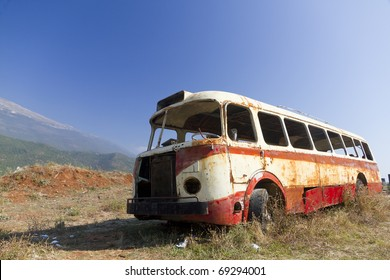 stripped rusty, old abandoned red bus wreck in arid mountainous landscape of Montenegro