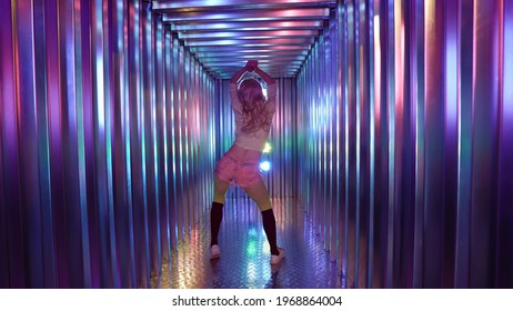 A stripper in fishnet tights and shorts. She has a sexy twerk booty dance in the studio in neon light, rear view.