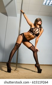 The stripper in lace lingerie dances by the pole