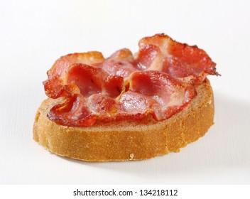 Strips of crispy fried bacon on a slice of bread