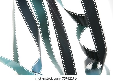 Strips of exposed unrolled 35mm film hanging down over a white background in a tangle in a conceptual image