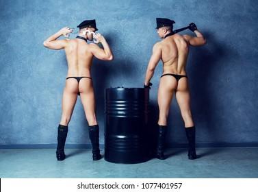 striptease dancers wearing costumes of policemen in the studio