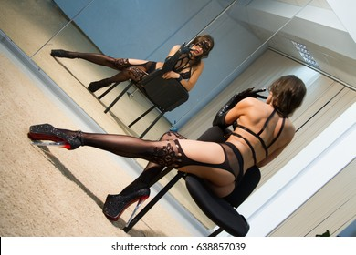 striptease in a stage suit sits on a chair in front of a mirror