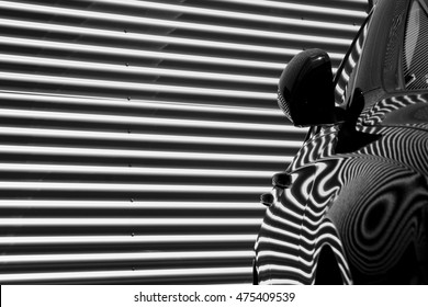 stripy garage door pattern making an abstract reflection on the side of a clean and glossy car