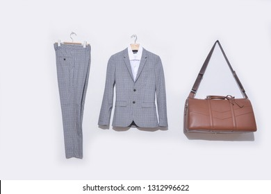 stripy suit, white shirt, and stripy  pants on hanging and leather handbag