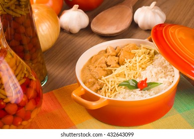 Stroganoff Chicken with rice over a wooden table. / Strogonoff