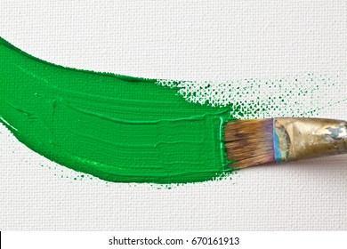 A stroke of green acrylic paint being applied to canvas.