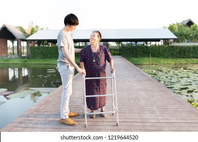stroke patient use walker, old Asian female train use walker with care giver, walk training, family time