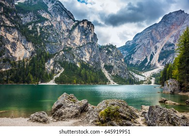 Stroll around the most beautiful alpine lake Lago di Braies. Travel to South Tyrol, Italy. The concept of walking and eco-tourism