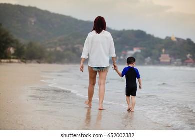 Stroll the beach as a family,Women, boys,Landscape sunset.