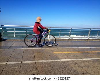 Strolling on the Seaside promenade in Beirut. Beirut, Lebanon - January 09, 2016: one girl's biking  walking via Beirut's famous seaside promenade, Lebanon