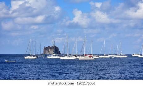 Strombolicchio sea stacks of volcanic origin and boats near volcano Stromboli,Lipari islands near Italy