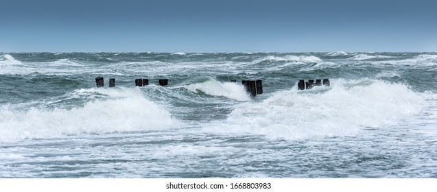 Stromy day on the beach, wooden Groyne in the waves of the raging sea - Shutterstock ID 1668803983
