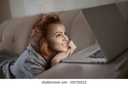 Strong addiction to the internet at night. Young girl smiling at her computer while watching media