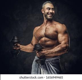 Starker, erwachsener, fit muskulöser Kaukasier-Trainer, der für ein Fotoshooting in einem dunklen Studio unter dem Rampenlicht steht und graue Sportbekleidung trägt, seine Muskeln zeigt und eine Hantel aufstellt, die fröhlich aussieht