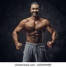 Strong, adult, fit muscular caucasian man coach posing for a photoshoot without his shirt in a dark studio under the spotlight wearing sporty shorts, showing his muscles looking powerful and smiling