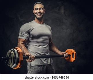 Strong, adult, fit muscular caucasian man coach posing for a photoshoot in a dark studio under the spotlight wearing grey sportswear, showing his muscles and holding a sport gear looking joyful