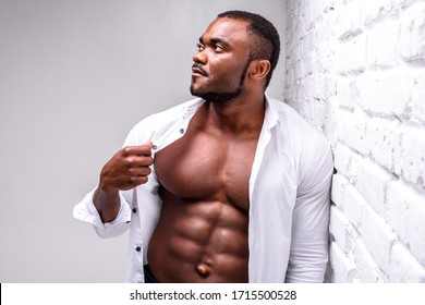 Strong african athlete in a white shirt. Posing showing perfect muscle shape near a white brick wall
