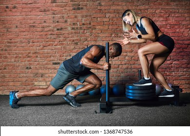 Strong african man pushing sled with weights in the gym having cross fit training while his personal caucasian female coach encouraging him in a gym.