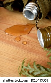 Strong alcohol drink is pouring out of an open flask on wooden background