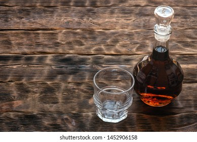 Strong alcohol in a transparent bottle and a drinking glass on a brown wooden table background.