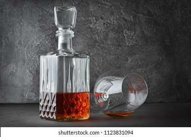 Strong alcoholic drink cognac in lying sniffer glass and crystal decanter on gray concrete background
