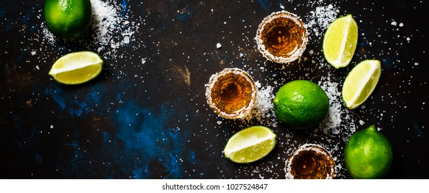 Strong alcoholic drink with salt and lime, dark background, top view