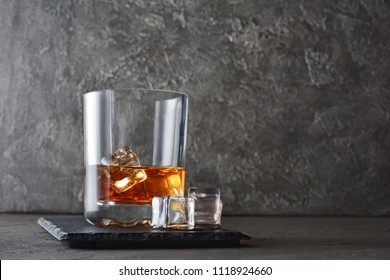 Strong alcoholic drink scotch whisky with ice cube in old fashion glass on gray concrete background