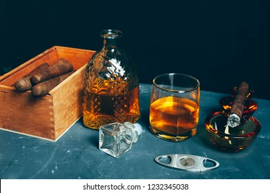 Strong alcoholic drink, scotch whisky in old fashion glass and decanter with smoking cigar in ashtray on gray concrete background
