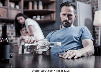 Strong alcoholic drink. Selective focus of vodka being poured into the glass by a sad depressed thoughtful man