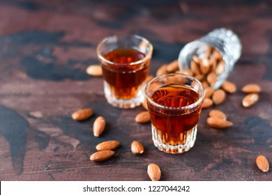 "strong alcoholic Italian liqueur ""Amaretto"" with almonds nuts on a wooden table, party at the bar,  menu for the bar, selective focus"