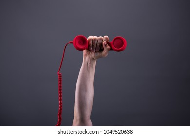 Strong arm and hand holds a red telephone up in the air