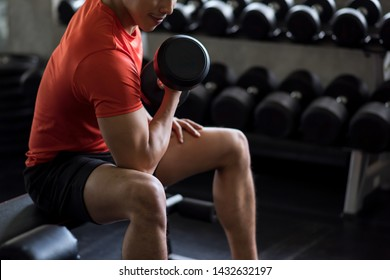 Strong Asian man bodybuilder sit and exercise biceps with heavy dumbbells with gym background. Muscular body sportsman in sport fitness center. Bodybuilding and healthy happy lifesytle concept.