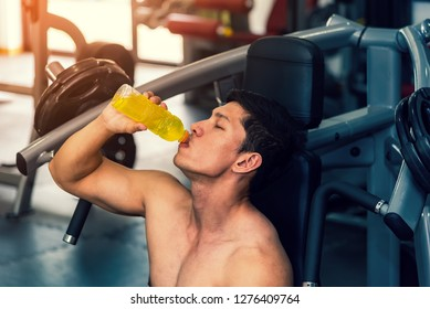 Strong asian man has muscle exercise in the fitness gym . Athletic handsome man having rest after bodybuilding training drinking electrolyte drink . Healthy sport energy drink concept
