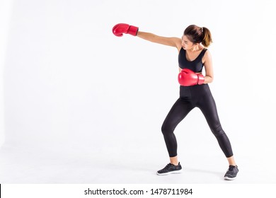Strong Asian woman in black sportswear and red boxing gloves punching isolated on white background with copy space. Young fit female doing boxing exercise