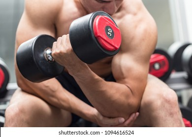 Strong Athletic Asian Man workout with dumbbell curl Concentration muscle upper arm for bodybuilding feeling so strong and powerful,Bodybuilder Concept