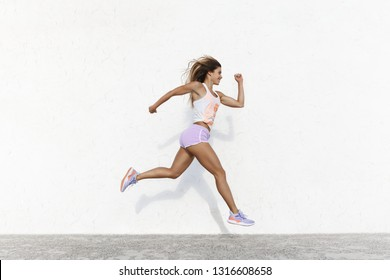 Strong athletic happy sportswoman wearing sport shorts jump across white concrete wall facing forward running in air, smiling accomplished, setting goal, workout, jogging, sprint along quay