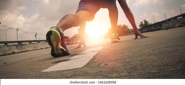 strong athletic legs of sport man, Athlete man in running pose on city street. Sport tight clothes. Bright sunset