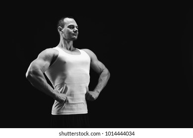 Strong athletic male, bodybuilder. Muscular body and strong shoulder muscles. Studio shot on black background, low key. Bodybuilding concept, black and white image