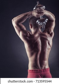 Strong athletic man with dumbbells behind his back against a dark background