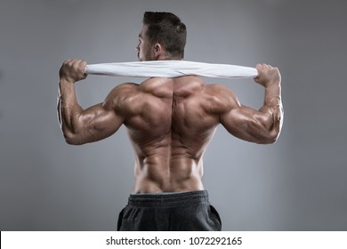 Strong Athletic Man Fitness Model posing back muscles, triceps, latissimus over white background