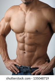 Strong Athletic Man Fitness Model Torso showing six pack abs.  Bodybuilder physique in jeans.