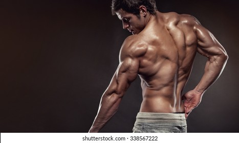 Strong Athletic Man Fitness Model posing back muscles, triceps, latissimus with copyspace