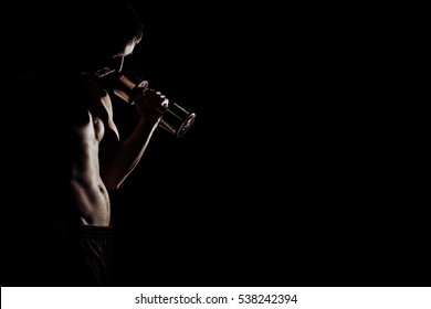 Strong Athletic Man Fitness Model Torso showing six pack abs. isolated on black background with copyspace Closeup of a handsome power athletic man bodybuilder doing exercises with dumbbell.