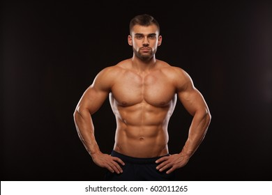Strong Athletic Man - Fitness Model showing his Torso with six pack abs. isolated on black background with copyspace