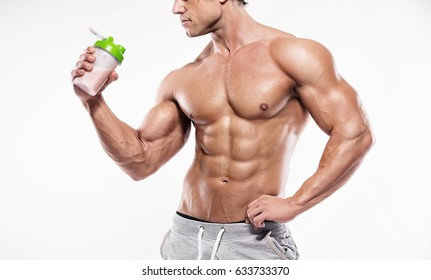 Strong Athletic Man Fitness Model Torso showing six pack abs. holding bottle of energy drink
